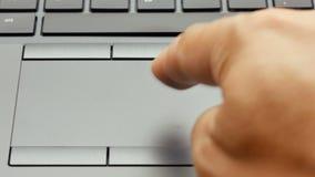 Primer encima de la mano masculina que golpea ligeramente y que enrolla el ordenador portátil del panel táctil o la cantidad del  metrajes