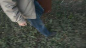 Primer encima de un hombre que camina con una maleta vieja almacen de video