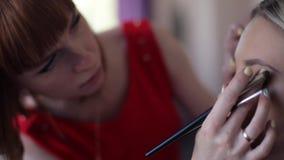 Primer Estilista del artista de maquillaje que hace el maquillaje para la muchacha de la moda almacen de metraje de vídeo