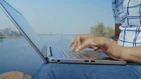 Primer, estudiante indio Hands Type Text en el teclado del ordenador portátil en Riverbank almacen de video