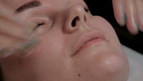 Primer estupendo de las manos del cosmetólogo con la manicura verde durante el procedimiento en el centro de la cosmetología Masa metrajes