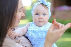 Primer europeo el otro pequeño niño femenino que se considera en vestido azul fotos de archivo