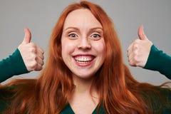 Primer extremo de la mujer con el pelo castaño que da el pulgar Fotografía de archivo libre de regalías