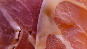 Primer extremo de rebanadas finas de jamón delicioso del cerdo en el plato 4k UHD almacen de metraje de vídeo