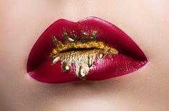 Primer femenino hermoso de los labios Lápiz labial rojo, pintura del oro que fluye sobre sus labios Foto común Foto de archivo