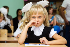 Primer graduador de la muchacha que se sienta en un escritorio en la primera lección Fotos de archivo