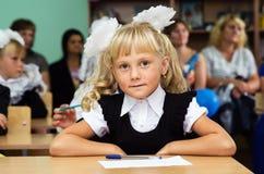 Primer graduador de la muchacha que se sienta en un escritorio en la primera lección Día del conocimiento Foto de archivo