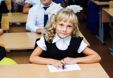 Primer graduador de la muchacha que se sienta en un escritorio en la primera lección el 1 de septiembre Fotografía de archivo