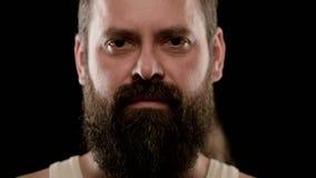 Primer grande de la cara dura de un hombre adulto barbudo con los ojos marrones almacen de video