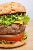 Primer grande del cheeseburger en la tabla de madera Imágenes de archivo libres de regalías
