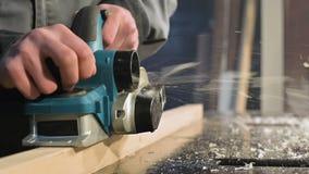 Primer grande Un carpintero que corta a un tablero de madera con un avi?n el?ctrico C?mara lenta de p?rticulas de polvo y de la h metrajes