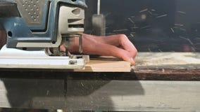 Primer grande Un carpintero que corta a un tablero de madera con un rompecabezas el?ctrico C?mara lenta de p?rticulas de polvo y  almacen de video
