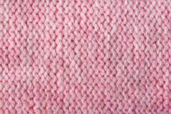 Primer hecho punto lanas rosadas del fondo del color Imagen de archivo