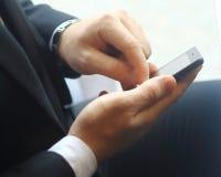primer hombre de negocios que mecanografía SMS en el smartphone Fotos de archivo libres de regalías