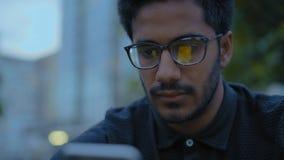 Primer, individuo indio en miradas de los vidrios en Smartphone, sentándose en el callejón en el parque almacen de video