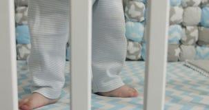 primer 4K de los pequeños pies del bebé que se colocan en el pesebre almacen de metraje de vídeo