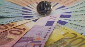 primer 4K de una moneda un euro con los billetes de banco de diversos valores Cobre el dinero almacen de video