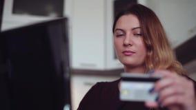 Primer La chica joven hermosa con un buen humor incorpora datos de la tarjeta de crédito en la tienda en línea Estilo casero almacen de video