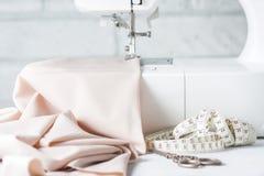 Primer la máquina de coser y el artículo de la ropa imagen de archivo libre de regalías