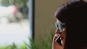 Primer La muchacha selecciona el contacto necesario en el listín de teléfonos del teléfono móvil y sonríe hablando con almacen de metraje de vídeo