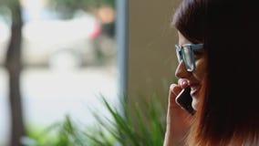 Primer La muchacha selecciona el contacto necesario en el listín de teléfonos del teléfono móvil y sonríe hablando con almacen de video