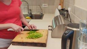 Primer la mujer corta la paprika verde en cocina del tablero de madera en casa metrajes