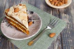 Primer la rebanada de torta de zanahoria con las almendras en un platillo en la tabla de madera fotografía de archivo libre de regalías
