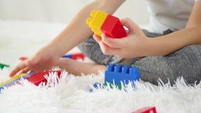 Primer: las manos del niño están jugando con los bloques del color en un fondo blanco Movimiento del resbalador de la cámara El c metrajes