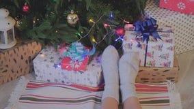 Primer Los pies de las mujeres en calcetines de la Navidad cerca del árbol de navidad holidays Los pies de las mujeres en el árbo almacen de metraje de vídeo