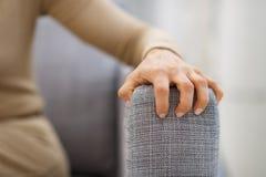Primer a mano de la mujer subrayada que se sienta en el diván fotos de archivo