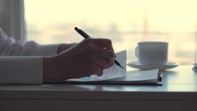 Primer, mano femenina, sosteniendo una pluma negra y escribiendo algo en documentos, mujer de negocios que trabaja con los gráfic metrajes