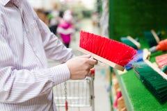 Primer a mano que selecciona o que elige y que compra una escoba arrebatadora para el piso o la trayectoria en la tienda de las c Imagen de archivo libre de regalías
