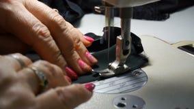 Primer Manos de la mujer que trabajan con la m?quina de coser Costura de la materia textil de la f?brica almacen de metraje de vídeo