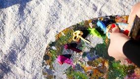 Primer, manos femeninas con la manicura roja brillante Paleta del arte El artista exprime un poco de pintura azul de un tubo ` S  almacen de video