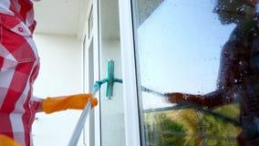 Primer, manos femeninas en los guantes que limpian, ventana que se lava por la fregona especial servicio de la limpieza almacen de metraje de vídeo