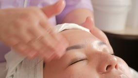 Primer Masaje de cara El cosmetologist profesional alisa la piel de una mujer de mediana edad asiática El movimiento de la cámara almacen de video
