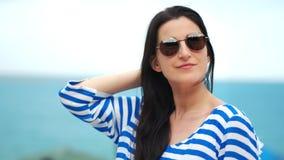 Primer medio de las gafas de sol que llevan de la mujer turística de moda en el fondo natural del cielo del mar almacen de video