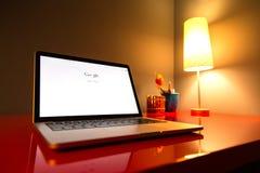 Primer moderno del ordenador portátil en el escritorio moderno rojo Imagen de archivo