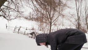 Primer, muchacha alegre en Hood Throws Snowballs en el bosque almacen de metraje de vídeo