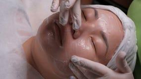 Primer Muchacha del este en el procedimiento del limpiamiento de la piel en el salón de belleza Las manos de un cosmetólogo profe metrajes
