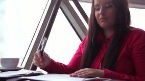 Primer Mujer de negocios joven que trabaja con los documentos de la oficina y que contesta a una llamada almacen de video