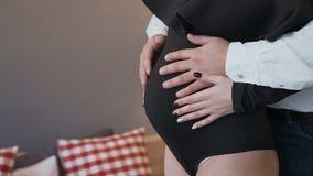 Primer Mujer embarazada con el marido que se coloca en la cama en el dormitorio y que lleva a cabo las manos en el vientre Concep almacen de metraje de vídeo