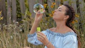 Primer, mujer hermosa de la cámara lenta que deja las burbujas de jabón que se sientan en la hierba cerca de la cerca de madera almacen de metraje de vídeo