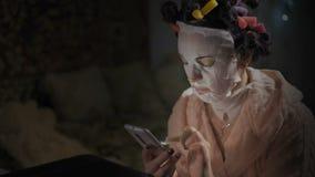 Primer, mujer hermosa en la máscara antienvejecedora que practica surf Internet en Smartphone metrajes