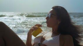 Primer, mujer hermosa en las gafas de sol que descansan sobre la orilla de mar que bebe de un tubo del cóctel metrajes