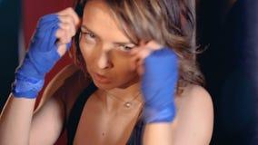 Primer Mujer joven confiada en los guantes de boxeo que encajonan mirando la cámara almacen de metraje de vídeo
