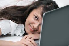 primer mujer joven sonriente con el ordenador portátil en el lugar de trabajo Fotos de archivo