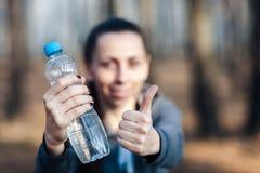 ¿Primer, mujer que sostiene una botella de agua y que muestra el pulgar para arriba? utdoors foto de archivo