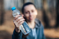 Primer, mujer que sostiene una botella de agua y que sonríe contra un fondo de la naturaleza foto de archivo libre de regalías