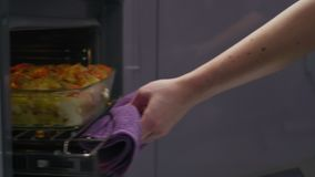 Primer, mujer sacar un plato con las pastas del horno almacen de metraje de vídeo